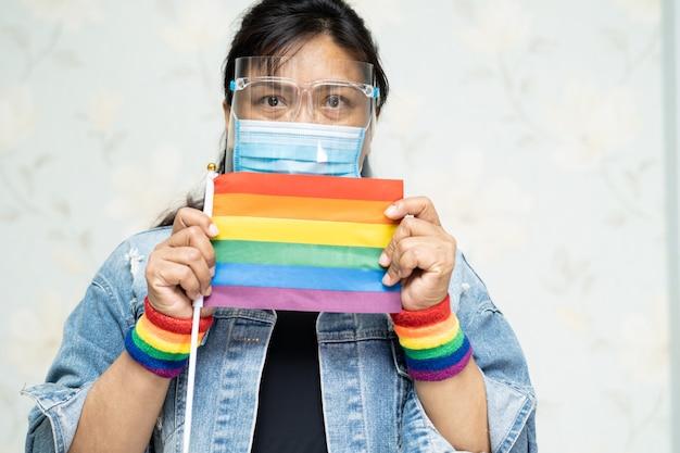 Asiatische dame, die regenbogenfarbflagge, symbol des lgbt-stolzmonats hält.