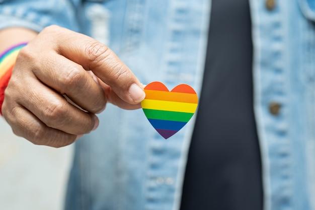 Asiatische dame, die regenbogenfarbflaggenherzensymbol des lgbt-stolzmonats hält
