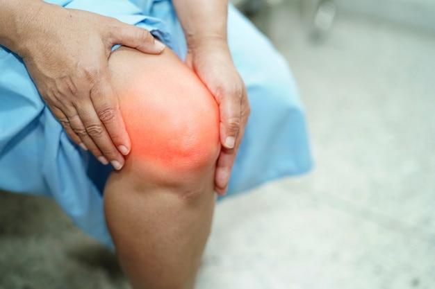 Asiatische dame-frau geduldige note von mittlerem alter und gefühl schmerzen ihr knie: gesundes medizinisches konzept.