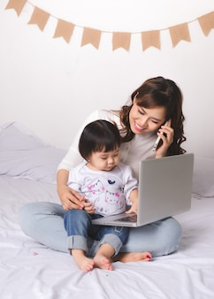 Asiatische dame im klassischen anzug spricht am handy und arbeitet zu hause mit ihrem baby am laptop.