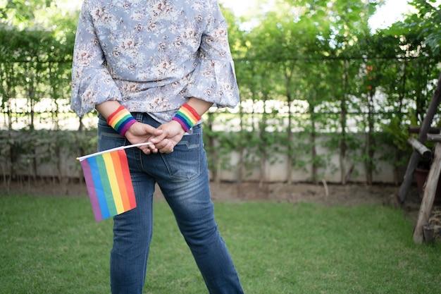 Asiatische dame mit regenbogenfarbenfahne, symbol des lgbt-stolzmonats, feiert jährlich im juni soziale der schwulen, lesben, bisexuellen, transgender, menschenrechte.