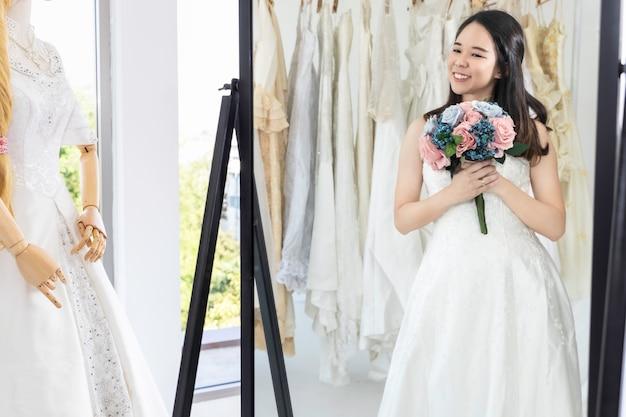 Asiatische dame schaut in den spiegel und lächelt, während sie brautkleider im geschäft wählt.