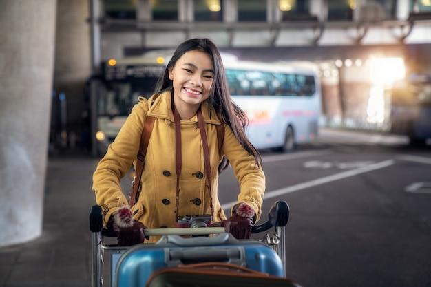 Asiatische dame tragen reisetasche im internationalen flughafen