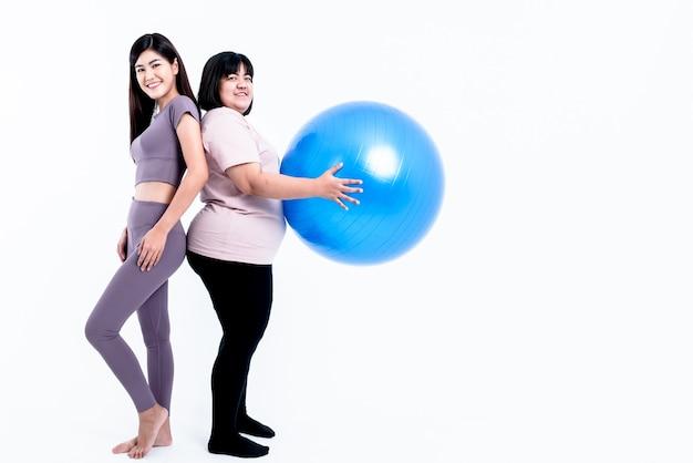 Asiatische dicke frau, die gymnastikbälle hält und attraktive frau in guter form, die sportkleidung trägt?
