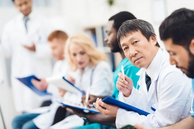Asiatische doktorkamera, die während des vortrags anstarrt.