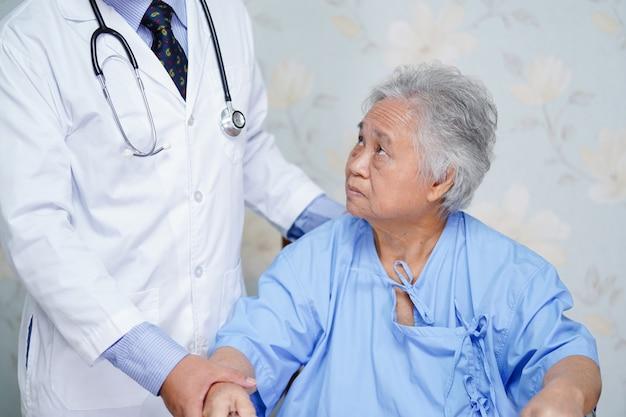 Asiatische doktorsorgfalt, -hilfe und -unterstützung älterer oder älterer frauenpatient alter dame an der krankenstation