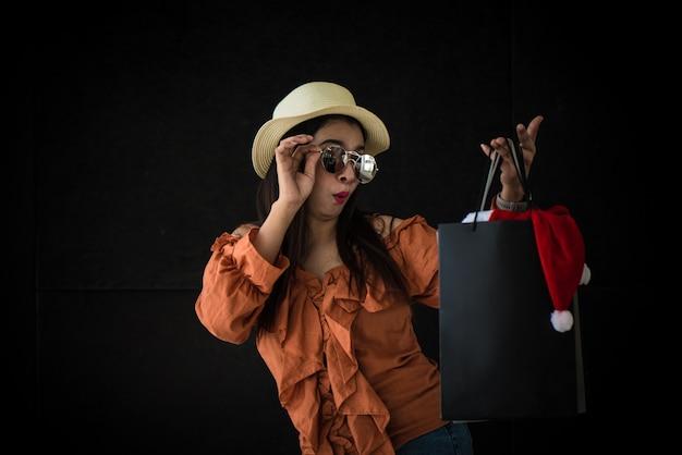 Asiatische einkaufsfrau überrascht mit black friday-einkaufstasche und santa claus-hut