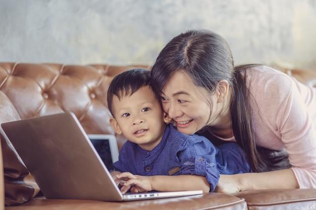 Asiatische einzelne mutter mit sohn schauen die karikatur über technologielaptop und spielen zusammen