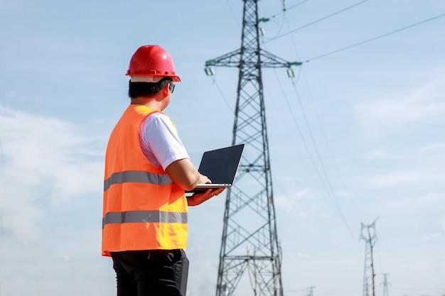 Asiatische elektroingenieure arbeiten in standardsicherheitsuniform, die ein mobiles stehen in einem kraftwerk verwenden, um den hochspannungsmast der elektrizität zu überprüfen.