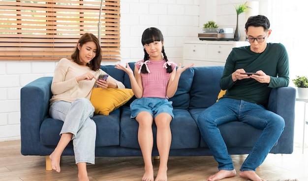 Asiatische eltern, die zu hause tabletten und handys benutzen, süchtig nach geräten, geräteabhängigkeit, übermäßiger gebrauch