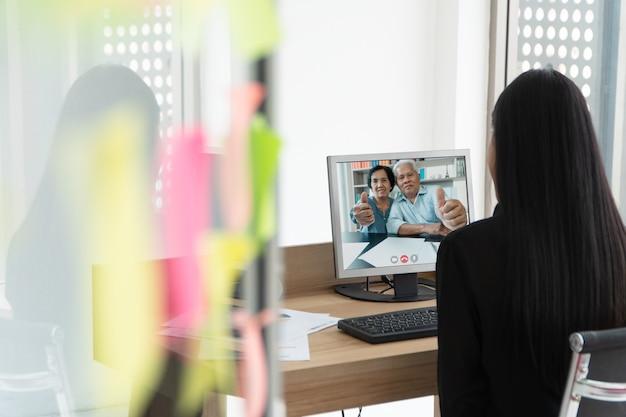 Asiatische eltern sind videokonferenz mit tochter im urlaub.
