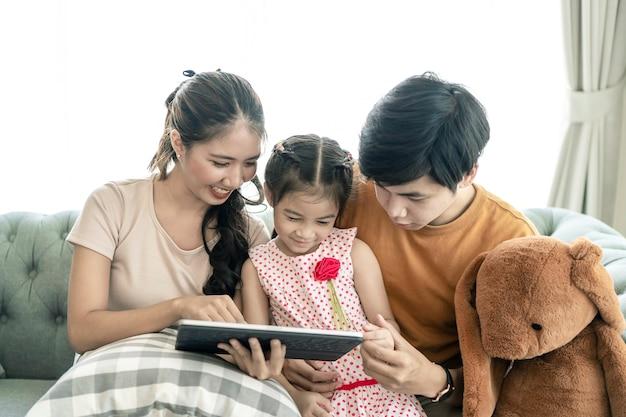 Asiatische eltern und ein kind schauen sich zu hause einen laptop an. familienkonzept.
