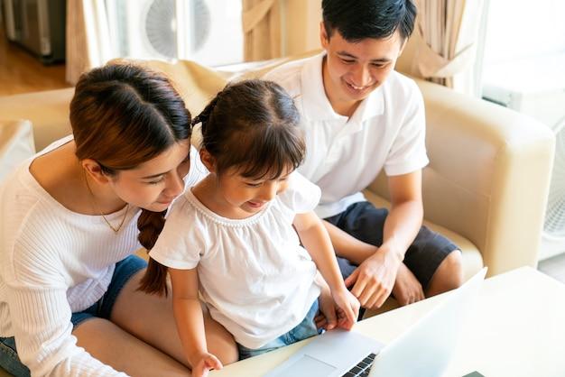Asiatische eltern unterrichten ihre tochter online zu hause. online-lernen und homeschooling