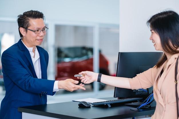 Asiatische empfangsdame, die den automatischen autoschlüssel für die prüfung in der wartungswerkstatt empfängt