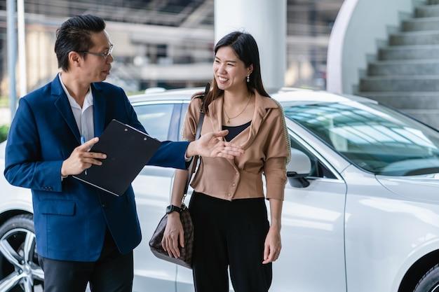 Asiatische empfangsdame, die den kunden begrüßt, um wartungsservice-mitte für das überprüfen des autos zu besichtigen