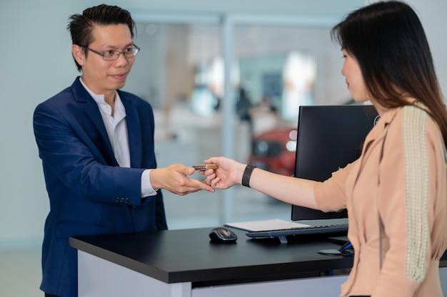 Asiatische empfangsdamenhand der nahaufnahme, die den automatischen autoschlüssel für die prüfung an der wartung empfängt