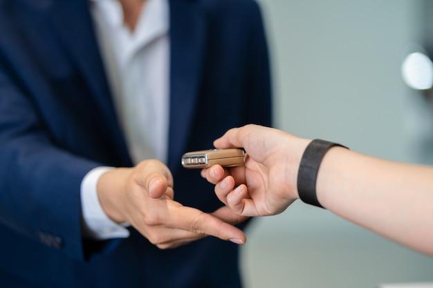 Asiatische empfangsdamenhand der nahaufnahme, die den automatischen autoschlüssel für die prüfung empfängt