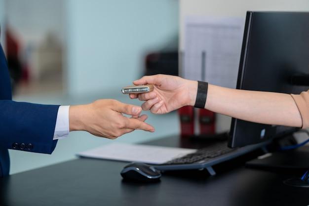 Asiatische empfangsdamenhand der nahaufnahme, die den automatischen autoschlüssel für die prüfung in der wartungsservice-mitte für im ausstellungsraum empfängt