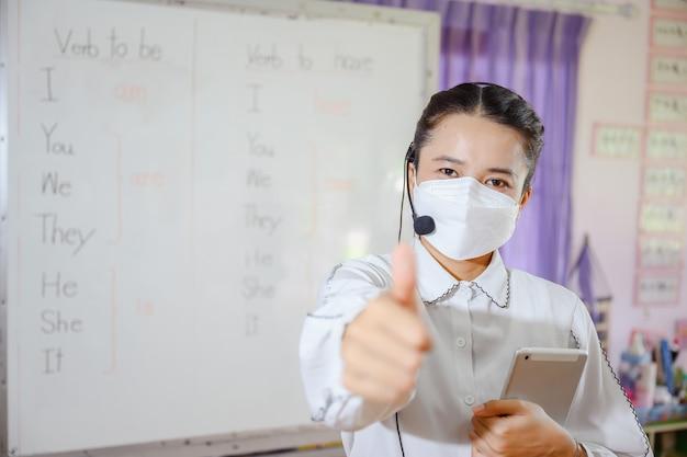 Asiatische englischlehrerin, die eine maske trägt und den schülern beibringt, online auf einem computerbildschirm zu lernen, indem sie ein online-videokonferenzsystem für die bildung verwendet