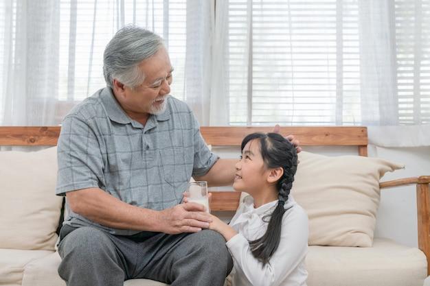 Asiatische enkelin, die dem großvater etwas milch gibt