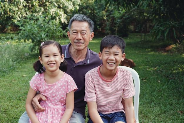 Asiatische enkelkinder, die mit ihrem großvater im park, glücklicher asiatischer älterer mann lachen