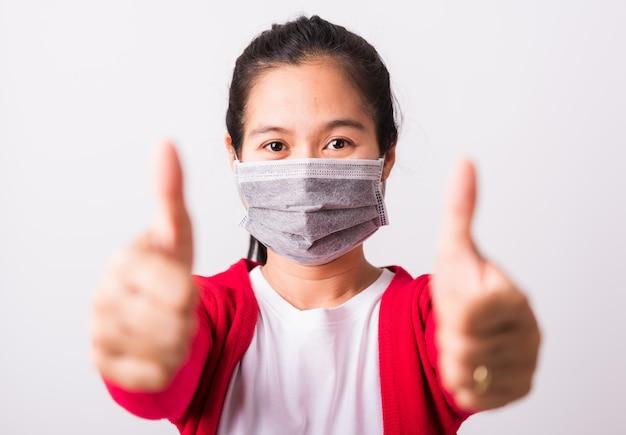 Asiatische erwachsene frau, die gesichtsmaske trägt, die gegen coronavirus schützt, zeigt fingerfinger oben für gutes zeichen