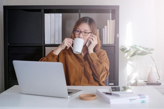 Asiatische erwachsene unternehmer arbeiten auf laptop und handy mit papierkram im intelligenten büro