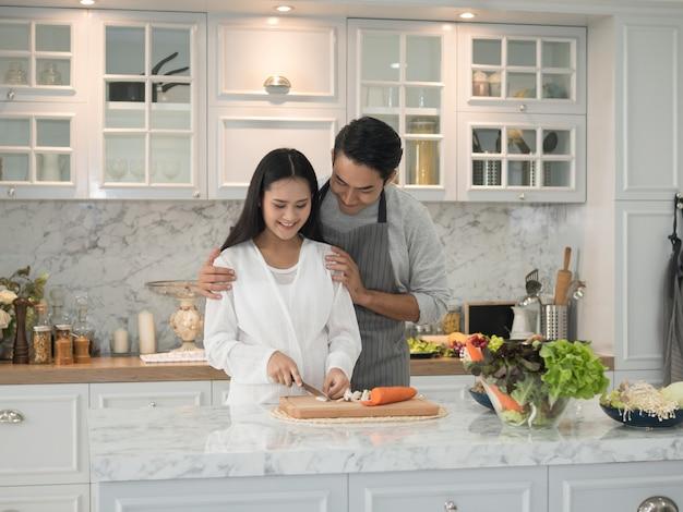Asiatische erwartende schwangere paare, die zusammen zu hause in der küche kochen