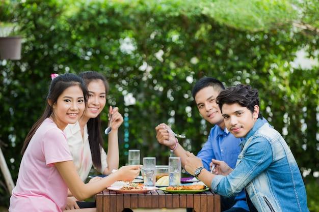 Asiatische ethnie, die zu hause im garten frühstückt. alle lachten und genossen