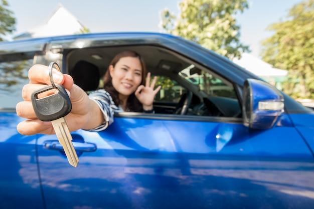 Asiatische fahrerfrau, die autoschlüssel zeigend lächelt