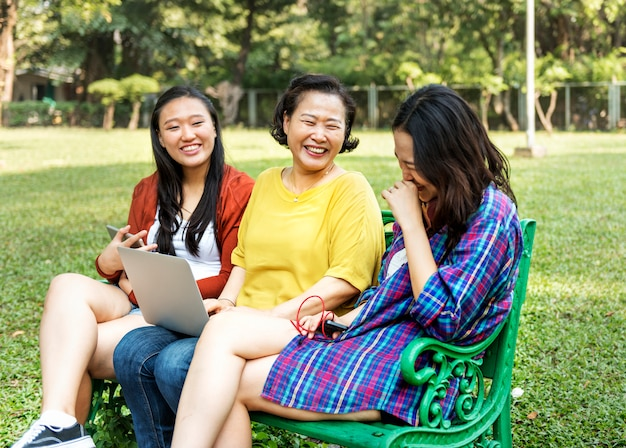 Asiatische familie benutzt digitale geräte am park