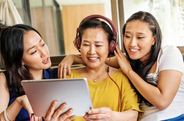 Asiatische familie benutzt digitale tablette zusammen