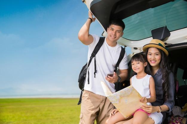Asiatische familie, die eine reisemutter und -tochter betrachtet karte plant