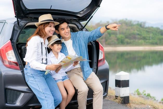 Asiatische familie, die im auto sitzt und auf die ansicht schaut