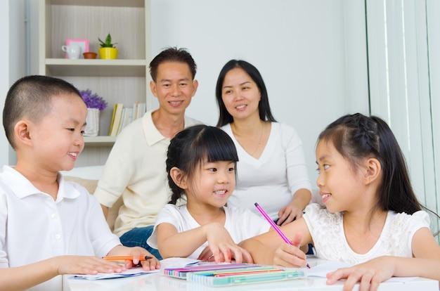 Asiatische familie, die schulhausarbeit am wohnzimmer tut