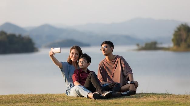 Asiatische familie drei mitglieder, mutter und zwei junge söhne, zusammen sitzend neben riesigem see mit bergen und wasser im hintergrund. sie verwenden ein smartphone, um selfie-fotos zu machen.