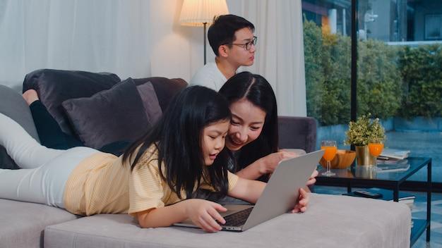 Asiatische familie genießen ihre freizeit entspannen zusammen zu hause. die lebensstilmutter und -tochter, die laptop verwenden, passen film im internet auf, vati sehen im wohnzimmer im modernen haus fern.