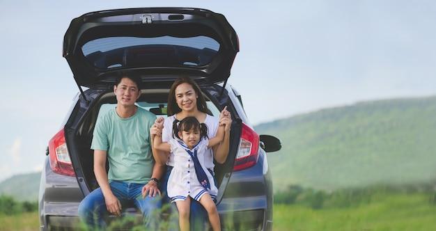 Asiatische familie. glückliches kleines mädchen mit der familie, die im auto sitzt. autoversicherungskonzept