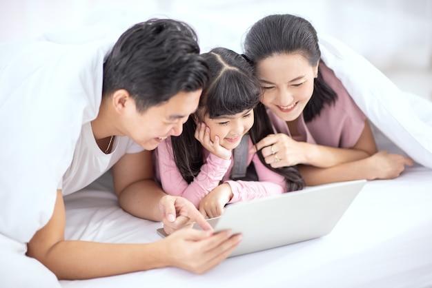 Asiatische familie lächelt und benutzt laptop-computer zusammen zu hause.