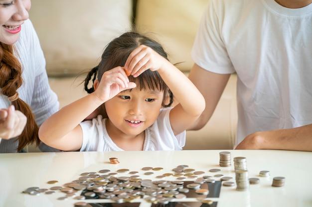 Asiatische familie lehren asiatisches süßes mädchen, das geld spart, das münzen in glasbank, weinlese-ton setzt