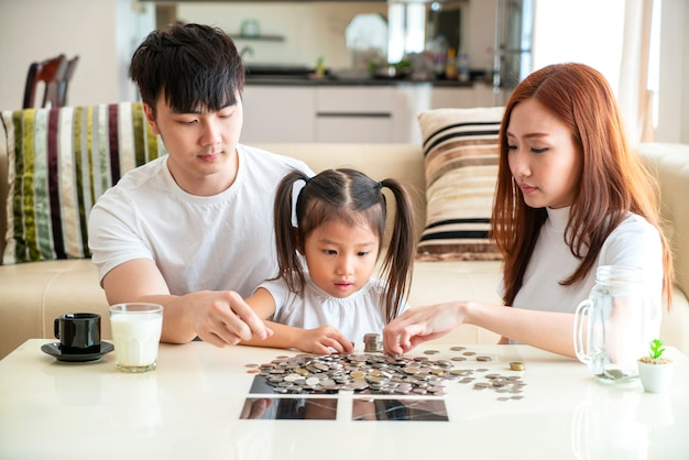Asiatische familie lehren asiatisches süßes mädchen, das geld spart, münzen in sparschweinbank zu setzen