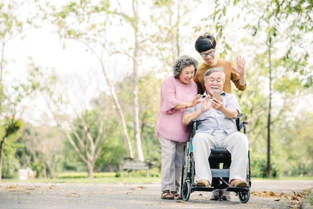 Asiatische familie mit jungem mann und älterer frau und mann im rollstuhl, die spaß haben