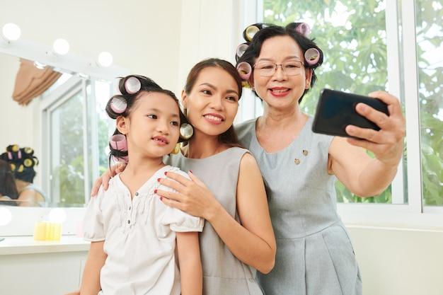 Asiatische familie mit lockenwicklern, die selbstporträt machen