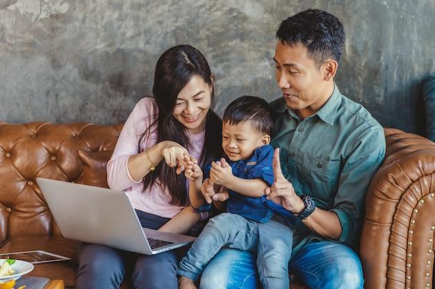 Asiatische familie mit sohn schauen die karikatur über technologielaptop und spielen zusammen
