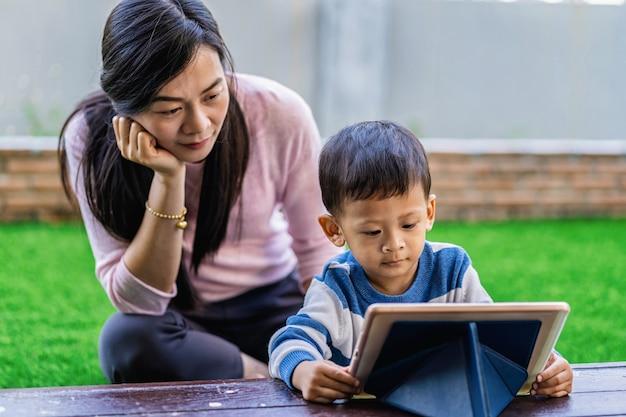 Asiatische familie mit sohn schauen die karikatur über technologietablette und spielen zusammen
