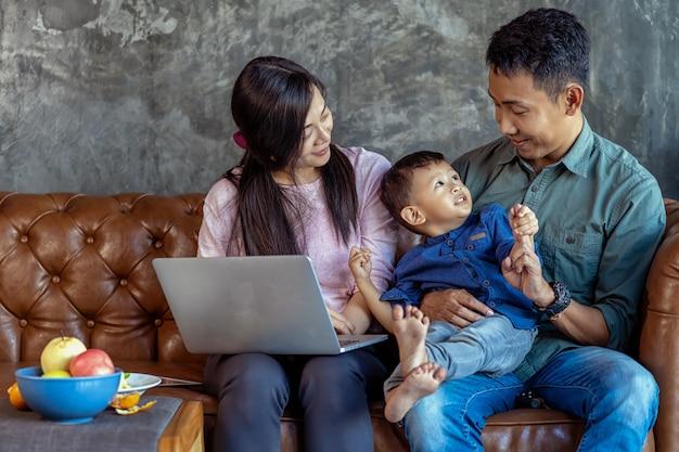 Asiatische familie mit sohn schaut die karikatur über laptop und spielt zusammen