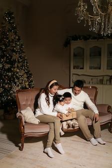 Asiatische familie mit zwei kindern öffnen geschenke, während sie nachts zu hause auf dem sofa am baum sitzen