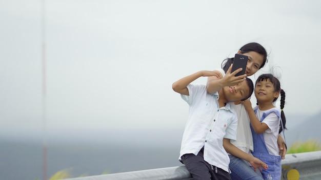 Asiatische familie, mutter, sohn und tochter, die zusammen selfie foto machen