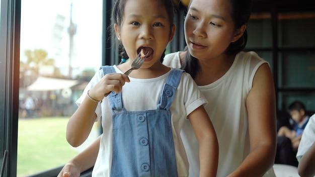 Asiatische familie, mutter und tochter essen glücklich würste