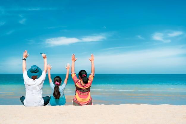 Asiatische familie sitzt entspannend auf weißem sandstrand mit türkisblauem meer im sonnigen tag, sommerreisekonzept